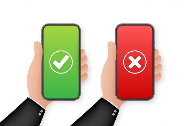 チェックマークが設定されたスマートフォンを持っている手。チェックマークとクロスチェック。図。 Premiumベクター