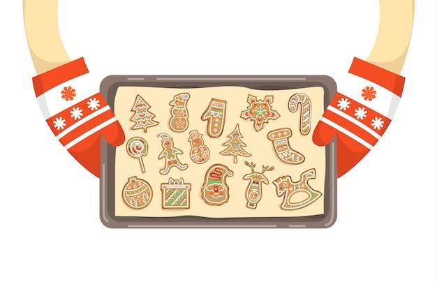 Руки в перчатках, держа поднос с домашним печеньем. традиционный праздничный имбирный пряник. иллюстрация Premium векторы