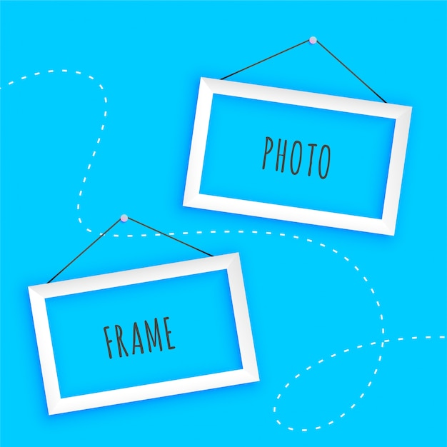 Hanging photo frames on blue background Free Vector
