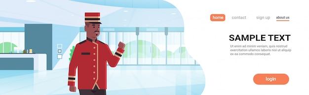 制服ホテルサービスコンセプトモダンなレセプションエリアロビーインテリアアフリカ系アメリカ人の漫画のキャラクターで幸せなベルマン男性労働者 Premiumベクター