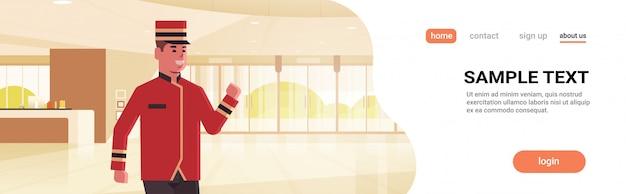 制服ホテルサービスコンセプトモダンなレセプションエリアロビーインテリア漫画のキャラクターで幸せなベルマン男性労働者 Premiumベクター