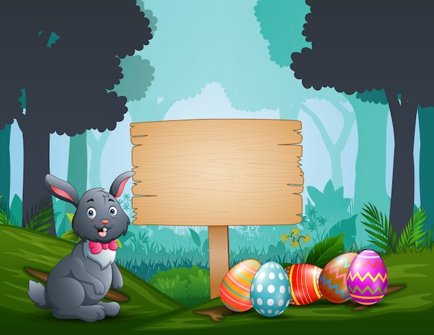 Счастливый кролик с пасхальными яйцами на деревянной доске Premium векторы