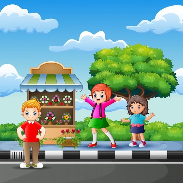 Happy children in front of the flower shop Premium Vector