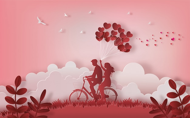Happy couple riding along on mountain with one hand holding heart shaped balloons. Premium Vector