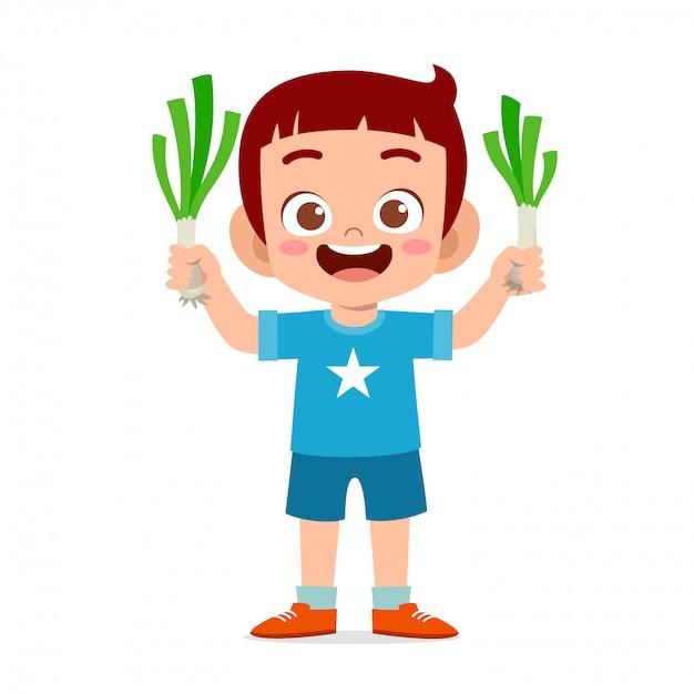 新鮮な野菜を持って幸せなかわいい子供男の子 Premiumベクター