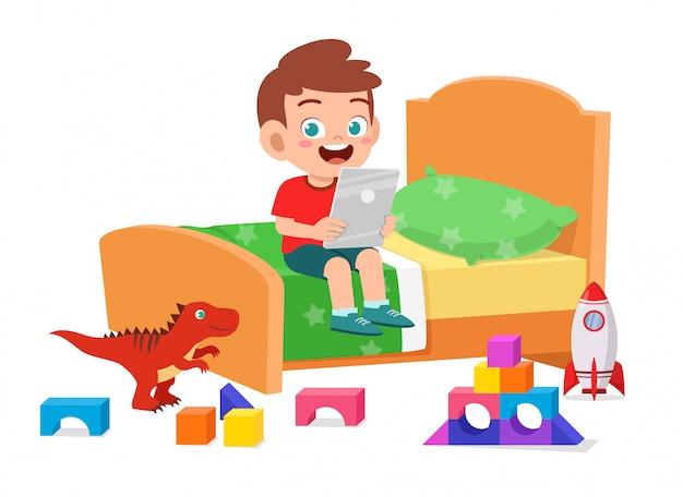 Счастливая милая игра мальчика маленького ребенка с таблеткой в комнате кровати Бесплатные векторы
