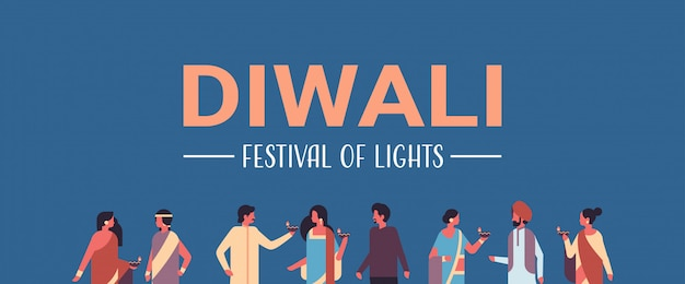 Happy diwali indian people group wearing national traditional clothes holding oil lamp banner Premium Vector
