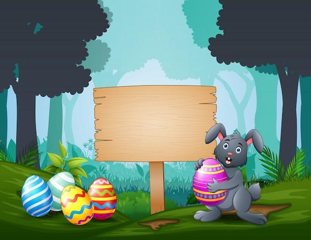 Счастливого пасхального кролика с пасхальными яйцами на деревянной вывеске Premium векторы