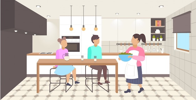朝食の母が彼女の息子と娘のダイニングテーブルモダンなキッチンインテリア漫画文字全長水平イラストに座って料理を提供する幸せな家族 Premiumベクター