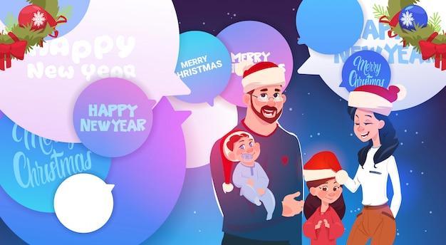 チャットの泡にメリークリスマスと新年のメッセージの上にサンタの帽子を着て幸せな家族 Premiumベクター