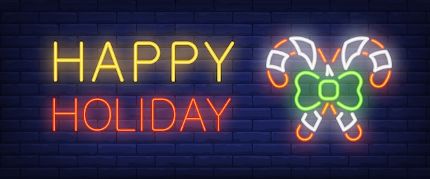 Happy holiday neon text and two candy canes Free Vector