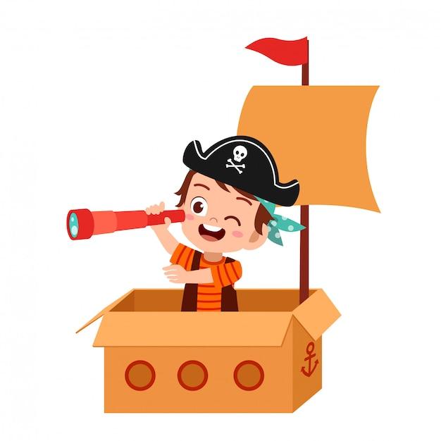 Happy kid boy play toy ship cardboard Premium Vector