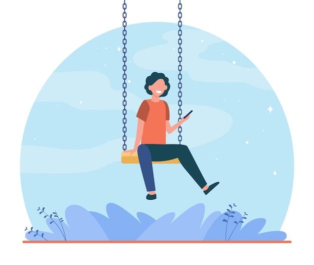 Bambino felice che si siede sull'altalena e tenendo il telefono. ragazzo, smartphone, gioco illustrazione piatta Vettore gratuito