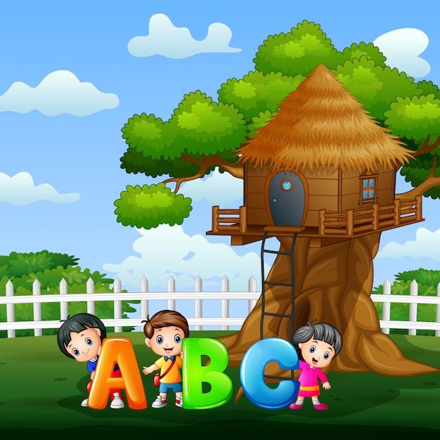 公園でabcテキストを保持している幸せな子供 Premiumベクター