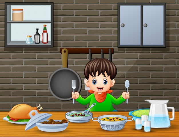 Happy little boy holding spoon and fork eating at the table Premium Vector