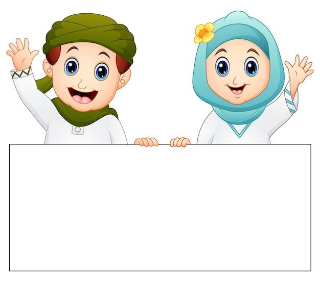 Happy muslim kid holding blank sign and waving hand Premium Vector