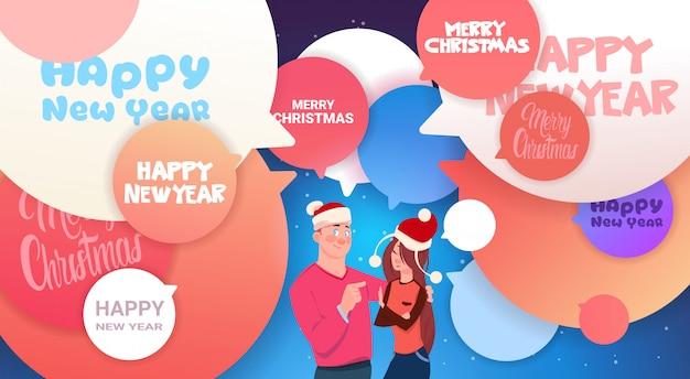 抽象的なチャット泡メリークリスマスの上のサンタ帽子の男女との幸せな新年バナー Premiumベクター