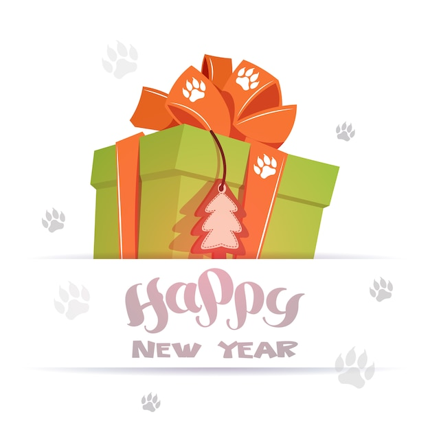 Happy new year greeting card big gift box over dog foot prints on background Premium Vector