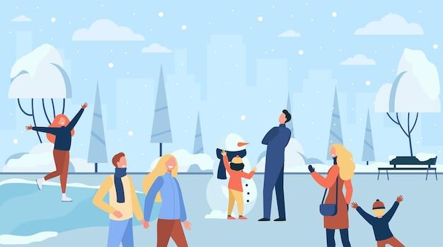 寒い冬の公園で歩く幸せな人々は、フラットなイラストを分離しました。漫画のキャラクターのアイススケート、遊び、家族作りの雪だるま 無料ベクター