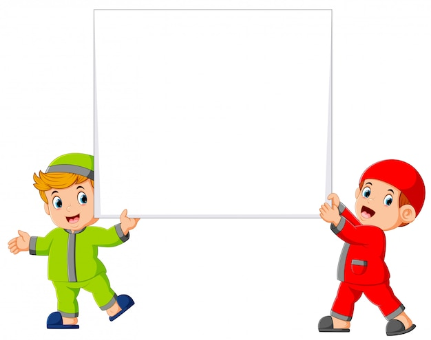 Happy two moslem boy holding big blank sign Premium Vector