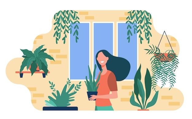 Piante d'appartamento in crescita della donna felice. personaggio femminile in piedi nell'accogliente giardino di casa e tenendo il vaso con la pianta. illustrazione vettoriale per il verde, hobby di giardinaggio, decorazioni per la casa, botanica Vettore gratuito