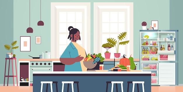 Happy woman preparing healthy food at home cooking concept modern kitchen interior horizontal portrait Premium Vector
