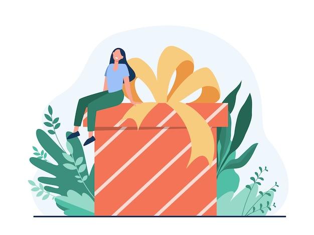 贈り物を受け取る幸せな女性。弓フラットベクトルイラストと巨大なプレゼントボックスに座っている小さな漫画のキャラクター。誕生日、サプライズ、クリスマス 無料ベクター