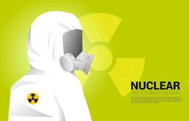 Белый костюм hazmat с полной маской и ядерным фоном. концепция радиоактивной опасности и ситуации с ядерной защитой Premium векторы