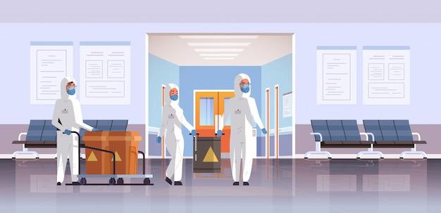 Люди в защитных костюмах hazmat, несущих бочки с предупреждающим знаком вспышка гриппа китайское возбудитель респираторный карантин коронавирус концепция больница интерьер горизонтальный Premium векторы