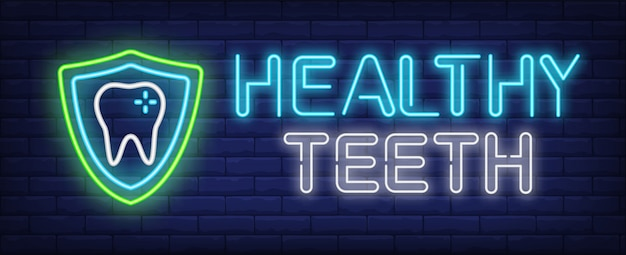 Healthy teeth neon text and tooth with protection shield Free Vector