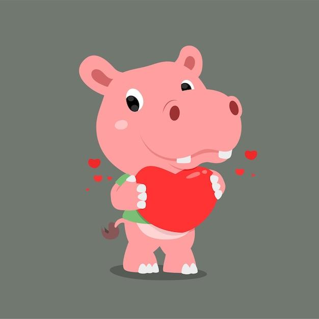 Бегемот с милым лицом держит в руке большое сердце Premium векторы