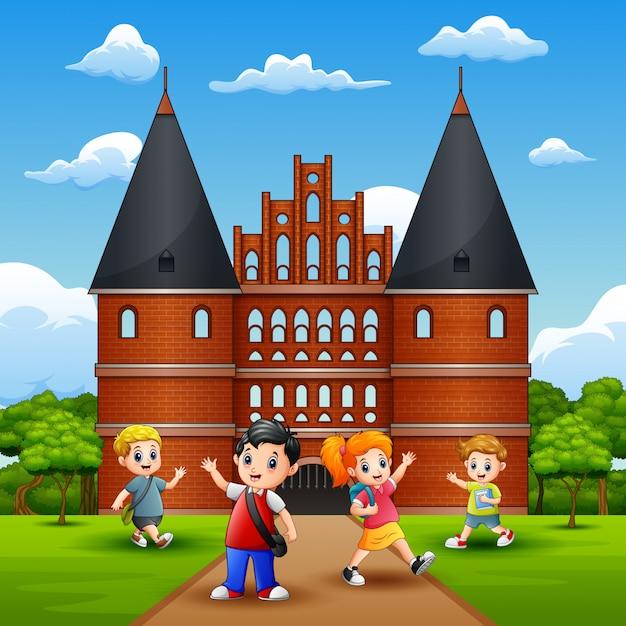 Holstentorの前で楽しいと笑っている幸せな学校の子供たち Premiumベクター