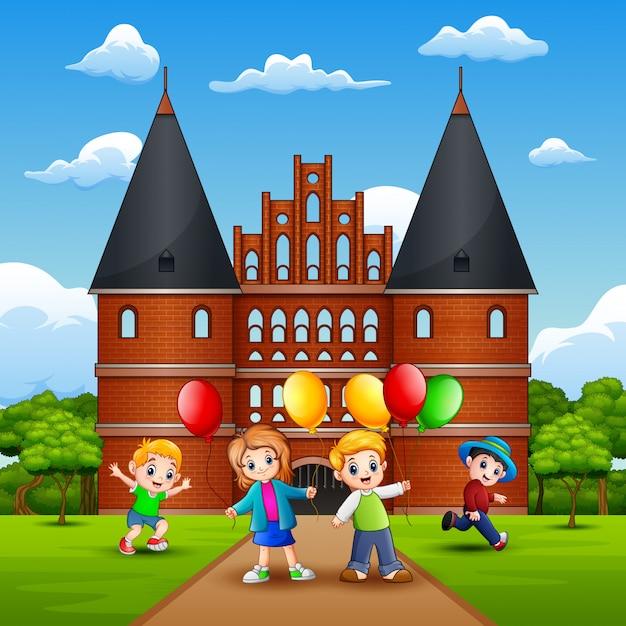 Holstentorの前で遊んでいる子供たち Premiumベクター