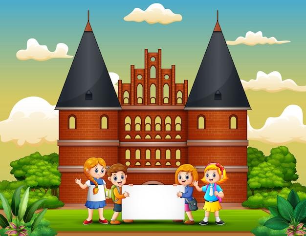 Holstentorの建物の前に空白の看板を持っている子供たち Premiumベクター