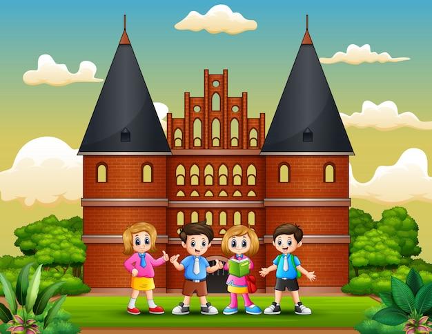 Holstentorの建物の前に立っている幸せな学校の子供たちの漫画 Premiumベクター