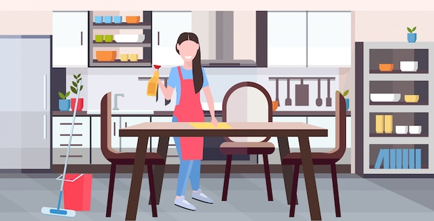 Housewife in apron wiping dinning table by dust cloth girl doing housework cleaning service housekeeping concept full length flat modern kitchen interior horizontal Premium Vector