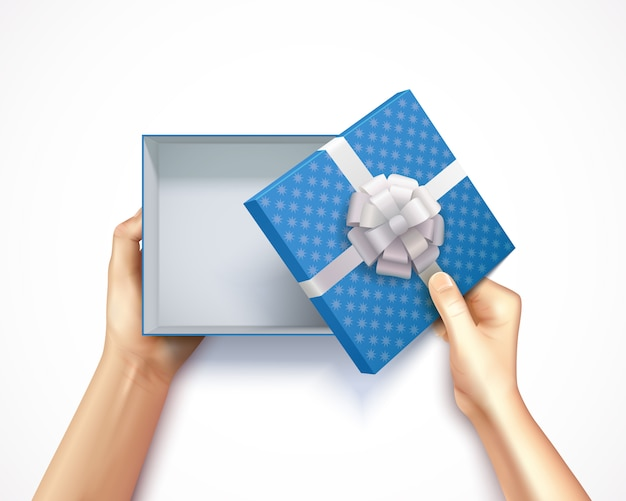 Human hands holding gift box top view realistic 3d square carton with blue polka dot Free Vector