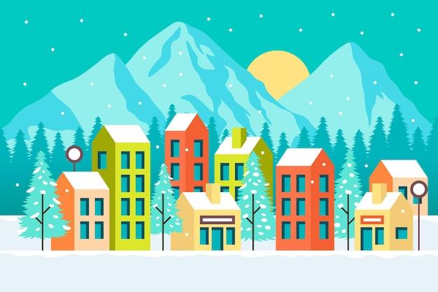 Иллюстрированный город со снегом и горами Бесплатные векторы