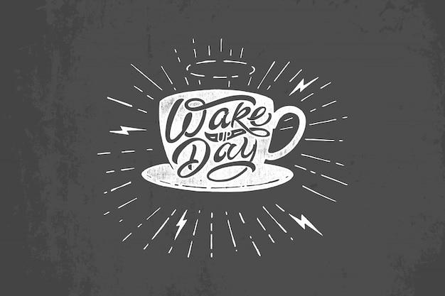 暗い灰色の背景に目を覚ます日のタイポグラフィとコーヒー・マグのイラスト。黒板にヴィンテージのレタリング。 tシャツ、メモ帳、ポスター、バナー、ポストカード、スケッチブックに印刷するためのテンプレート。 Premiumベクター