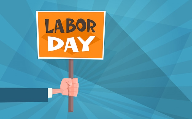 International labor day in vintage style greeting card with hand holding placard Premium Vector