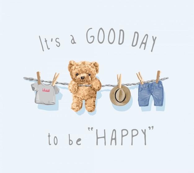 幸せな一日になりますように、かわいいクマのおもちゃとロープのイラストに掛かっている服のスローガン Premiumベクター