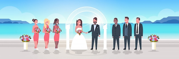 Just married bride and groom with bridesmaids groomsmen standing together on sea beach near arch wedding ceremony concept sunrise mountains background full length horizontal Premium Vector
