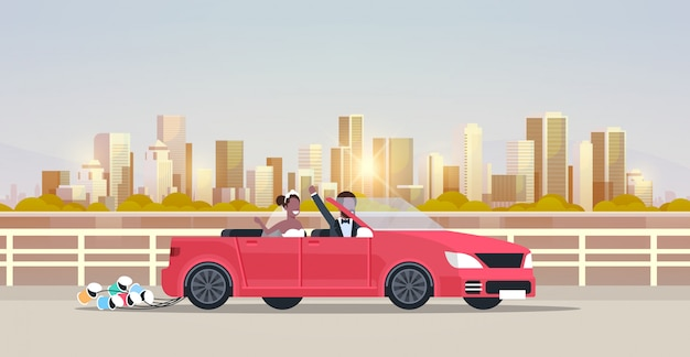 Just married bridegroom bride on road trip driving convertible car   couple in love wedding day concept cityscape background horizontal flat Premium Vector