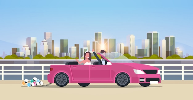 Just married bridegroom and bride on road trip driving convertible car romantic couple man woman in love wedding day concept modern urban city buildings cityscape background horizontal Premium Vector
