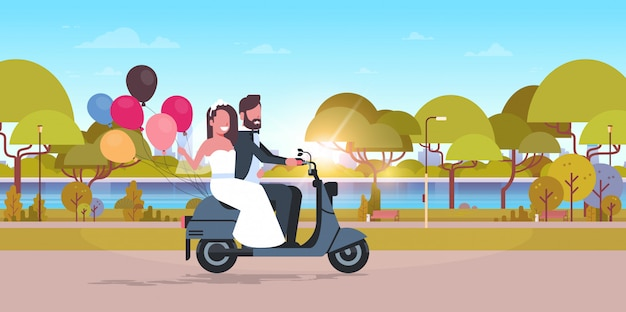 Just married couple riding motor scooter with colorful balloons bride and groom having fun wedding day concept city urban park landscape background full length horizontal Premium Vector