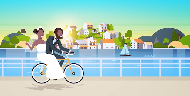 Just married man woman riding bicycle romantic   couple bride groom cycling bike having fun wedding day concept mountain city island background full length horizontal flat Premium Vector