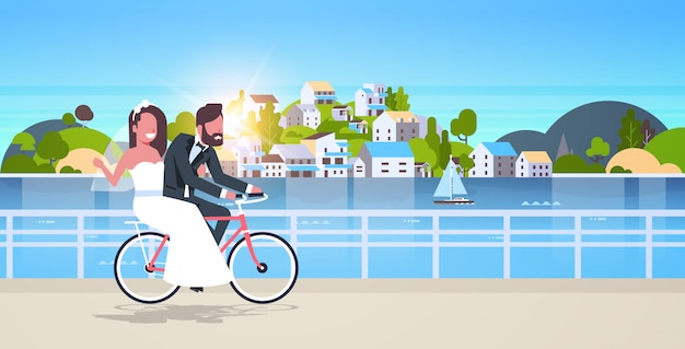 Just married man woman riding bicycle romantic couple bride and groom cycling bike having fun wedding day concept mountain city island sunset background full length horizontal Premium Vector