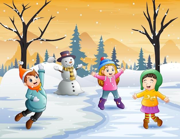 子供たちは雪の中でとても楽しく遊んでいます Premiumベクター