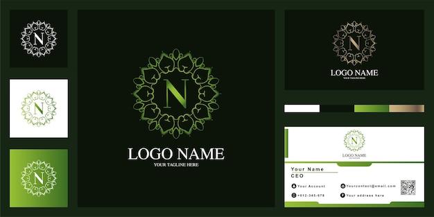 名刺と文字n高級飾りフラワーフレームロゴテンプレートデザイン。 Premiumベクター