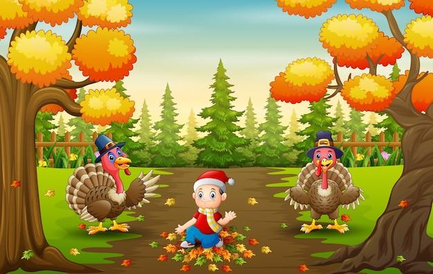 落ち葉で遊ぶ小さな男の子と七面鳥の鳥 Premiumベクター